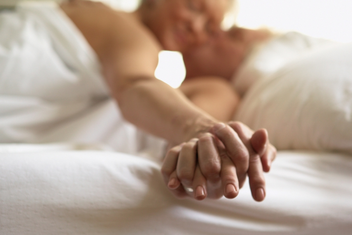 Photo shows an older couple lying in bed holding hands. According to recent studies, people over 50 are still having a lot of sex.