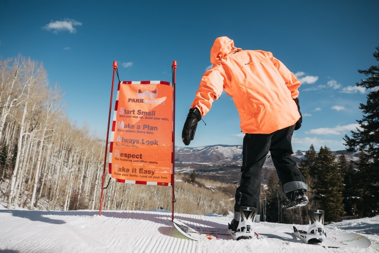 Pro snowboarder Brock Crouch riding Burton Step On strapless bindings. Here he's pictured in an orange winter jacket on the top of a snowy mountain in Aspen, Colorado next to an orange sign.