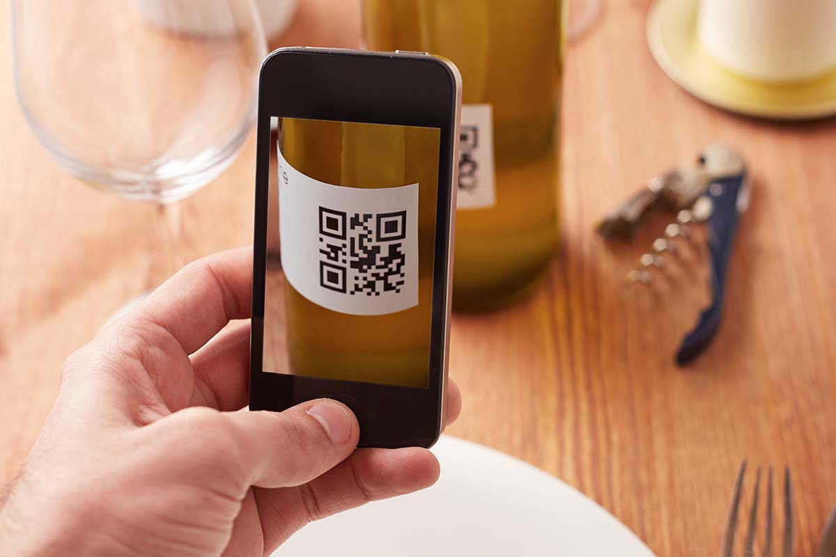 A phone reading a QR label on a bottle of wine. This standard, called U-Label, is coming to bottles in the EU this fall.