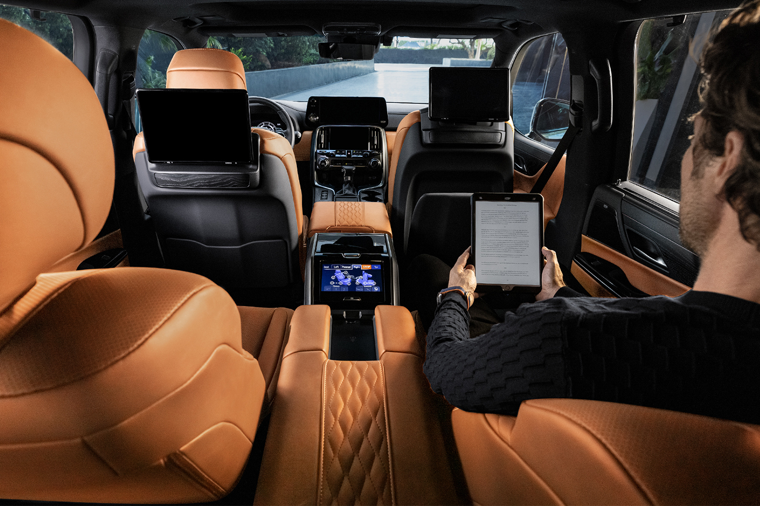 A man sitting inside the Ultra Luxury trim 2022 Lexus LX 600 SUV with two rear VIP seats that offer better legroom and air conditioning