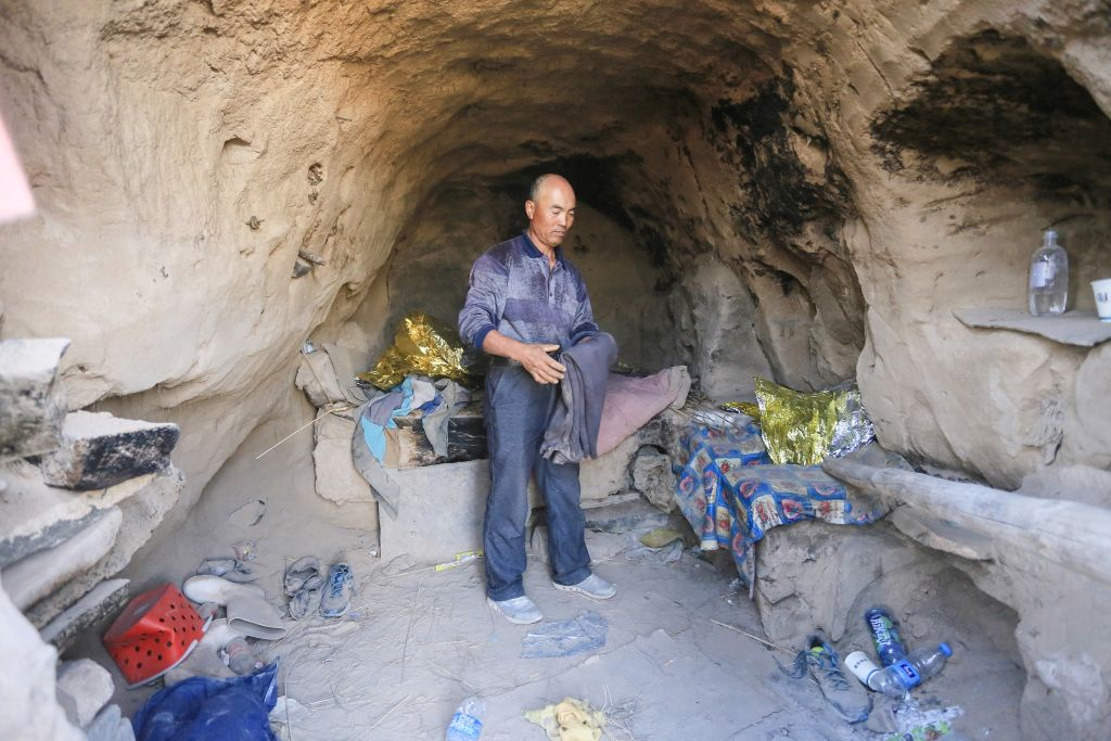 Shepherd Zhu Keming, hailed as a hero in China for rescuing six ultramarathon runners when extreme weather hit the area leaving at least 20 dead, showing the cave dwelling where he sheltered the stricken athletes near the city of Baiyin.