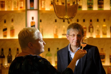 Emma Walker succeeds Jim Beveridge OBE becoming the first female Master Blender in the 200-year Johnnie Walker story. Here they are at a bar with Walker swirling Scotch in a glass.