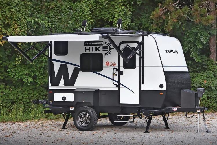 The new Hike 100 travel trailer from Winnebago sitting on a gravel plot in the woods